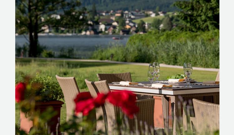 gedeckter Tisch mit Gläser, Stühle, im Hintergrund Blick auf den See und die Landschaft. (© Lackner)