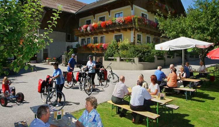 Der Gastgarten mit Tischen und Bänken lädt zum gemütlichen Beisammensein ein. (© www.mondsee.at)