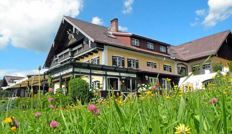 Blick auf den Riesnerhof, im Vordergrund eine Blumenwiese. (© www.mondsee.at)