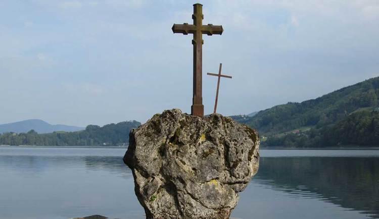 Blick auf einen Stein, auf dem ein Kreuz ist. Dieser Stein befindet sich im See. (© www.mondsee.at)