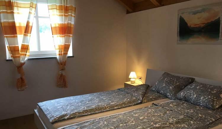 Schlafzimmer mit Doppelbett, Nachtkästchen, Bild an der Wand und Fenster mit Vorhängen