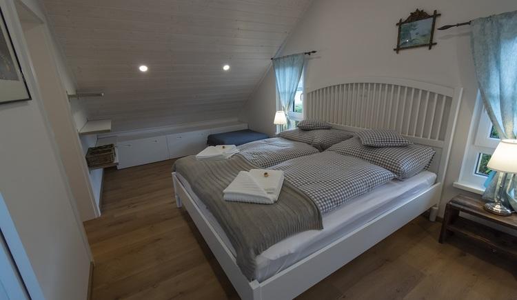 Auch im Schlafzimmer des Obergeschoss dominiert das Material Holz bei der detailreichen Gestaltung der Innenaustattung.