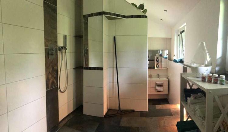 Geräumiges Badezimmer mit Dusche, Waschmaschine, Badewanne und Doppelwaschbecken.