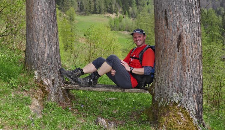 Bergwanderführer Herbert Benedik auf einer Bank zwischen zwei Bäumen.