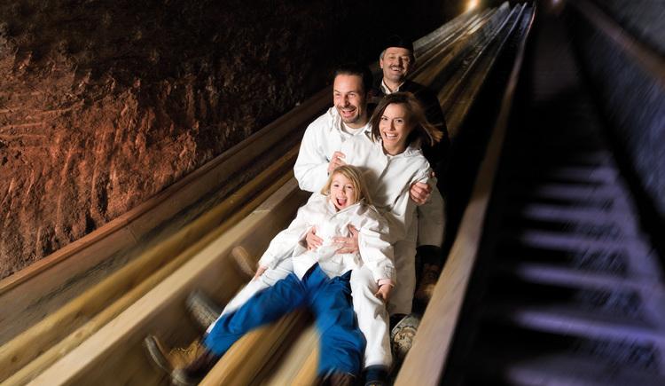 Auf dem Foto sieht man eine Familie die Bergmannsrutsche in den Salzwelten Hallstatt hinunterrutschen. (© Salzwelten Hallstatt-Bergauer)