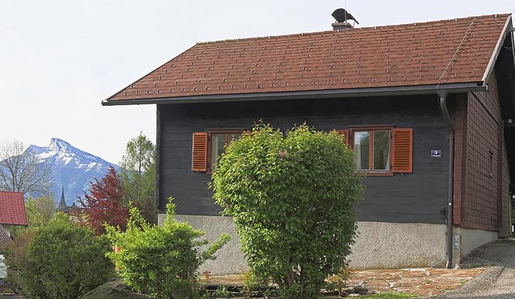 Blick auf das Haus von der Seite, im Hintergrund Berge
