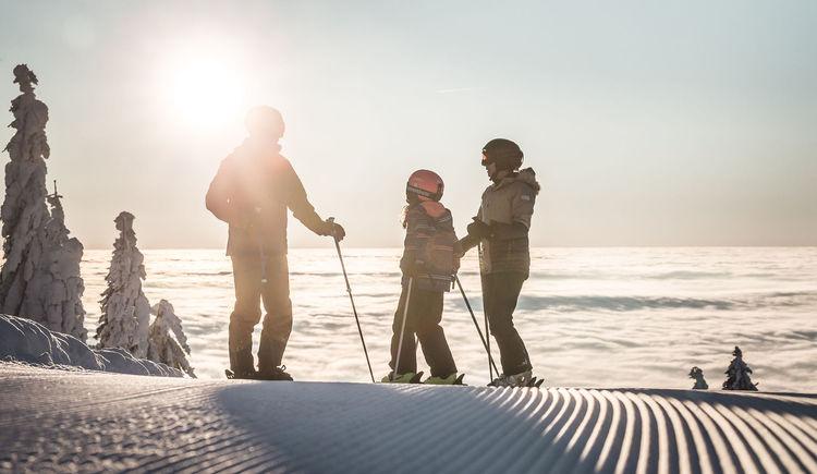 Familie mit 3 Personen auf einer Skipiste mit Sonnenuntergang.