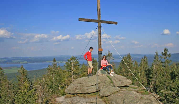 Aussichtsfelsen Bärenstein mit Gipfelkreuz und Blick zum Moldaustausee in Tschechien.