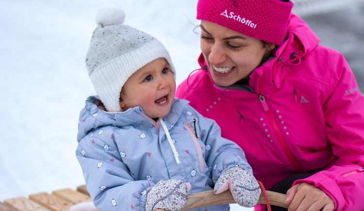 Woman with child in the snow. (© TVB Mondsee-Irrsee)