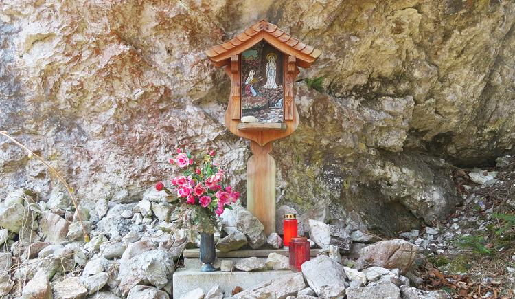 Kleiner Bildstock mit Blumen und Kerzen am Fuße der Drachenwand.
