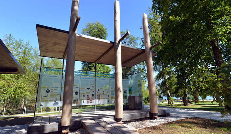 Holz Pavillon, im Hintergrund Tafeln mit Informationen zu den Pfahlbaudörfern. (© Tourismusverband MondSeeLand)