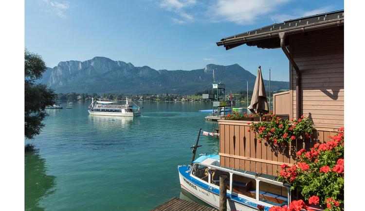 Blick auf den See mit Schiffen, im Hintergrund die Berge. (© Seepension Hemetsberger)