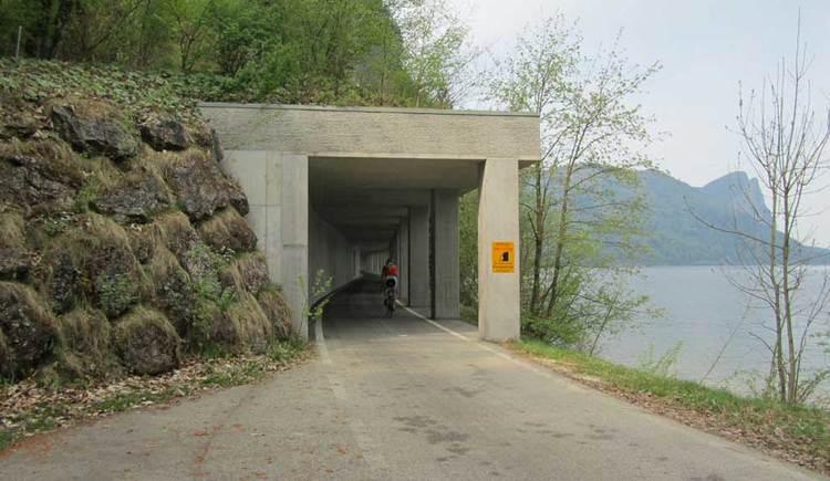 Blick auf den Fahrradtunnel, auf der einen Seite ist der See, im Hintergrund die Berge. (© www.mondsee.at)