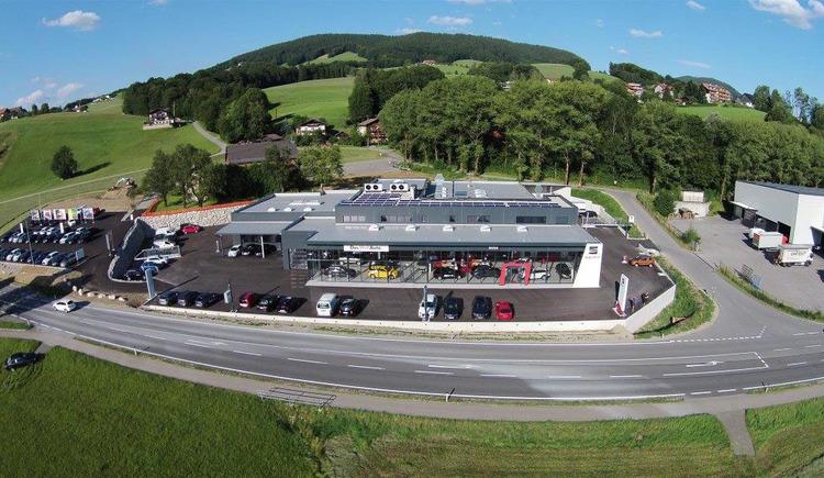 Luftaufnahme, Blick auf das Autohaus, im Vordergrund eine Straße, parkende Autos, im Hintergrund Landschaft. (© Autohaus Reiser)