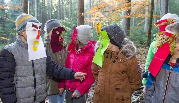 Ein Gruppe Kinder im Wald stehend mit selbstgebastelten Gesichtsmasken. (© www.naturschauspiel.at)