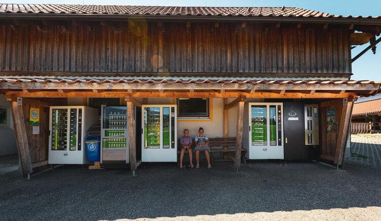 Gebäude mit 2 Personen auf einer Bank mit Verklaufsautomaten. (© Aubauer)