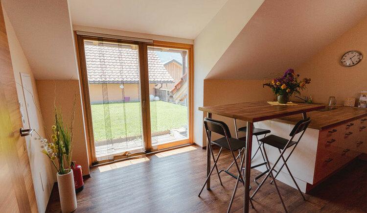 Tisch mit Stühlen, großes Fenster uund Dekovasen an der Seite. (© Seminar- und Biobauernhof Aubauer)