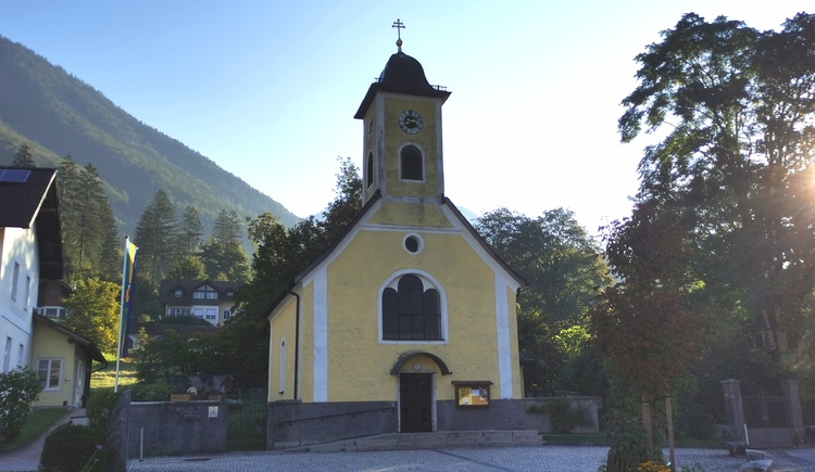 Das Bild zeigt die katholische Kirche von Obertraun mit dem kleinen Vorplatz. (© Ferienregion Dachstein Salzkammergut)