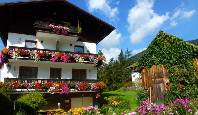 Unser Haus in der Sommerpracht. Die Balkone sind mit vielen bunten Blumen dekoriert. (© Eveline Glöckl)