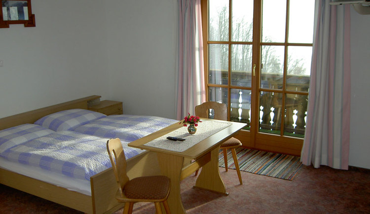 Double bed with nightstand, infront of it there is a small table with two chairs. Through the french window you can see the balcony.
