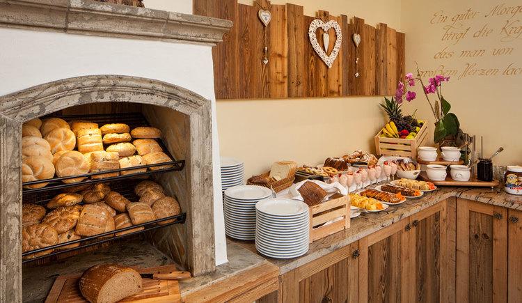 Frühstücksbuffet mit Gebäck, Tellern, Süßspeisen und Obst
