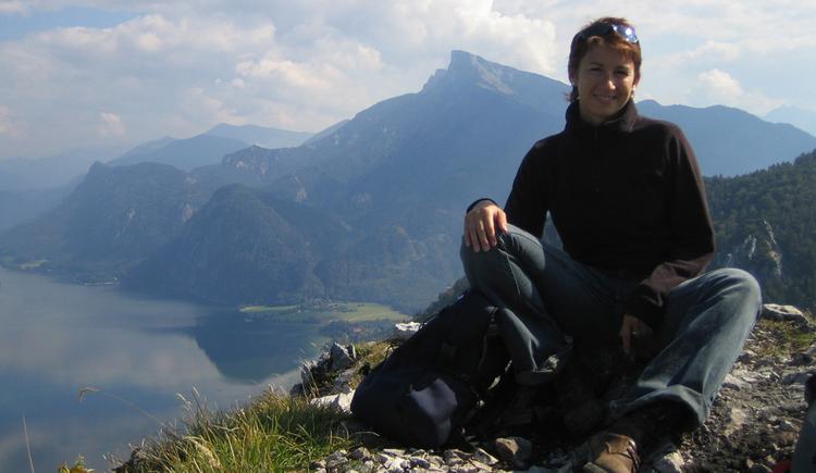 Frau sitzend auf dem Gipfel (Hausberg) mit Blick auf die Berge und dem See im Hintergrund. (© Fam. Winklhofer)