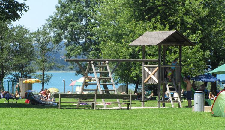 Blick auf den Badeplatz mit Spielgeräten, Bäume, im Hintergrund der See. (© Tourismusverband MondSeeLand)