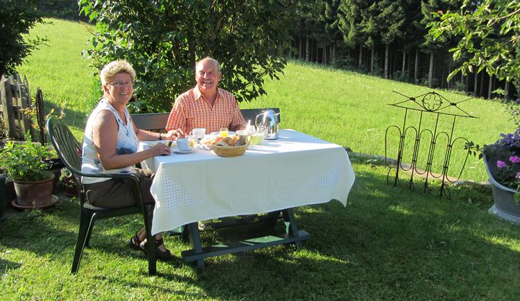 Frühstückende Gäste sitzen gemütlich im Garten. (© Langwallner)