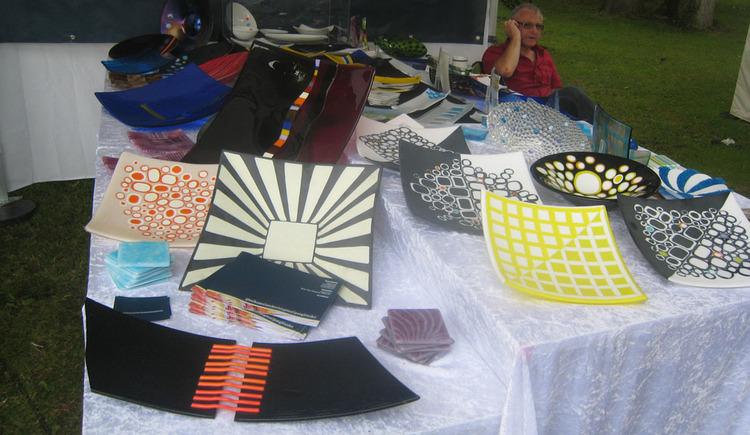 verschiedene Keramik-Deko-Artikel auf einem Tisch, im Hintergrund eine sitzende Person