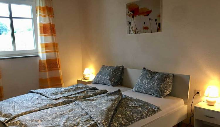 Bedroom with double bed, nightstands, picture on the wall and window with open curtains