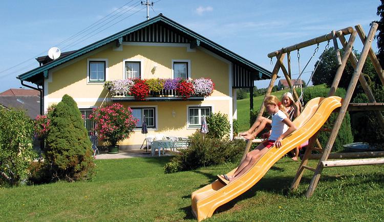 Blick auf das Ferienhaus, im Vordergrund Garten mit Schaukel, Rutsche und Kinder. (© Maier)