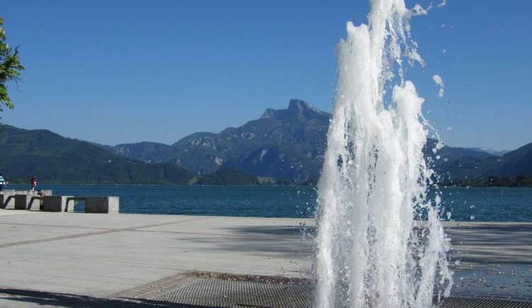 Blick auf den Springbrunnen bei der Seepromenade, im Hintergrund der Schafberg und der See. (© www.mondsee.at)