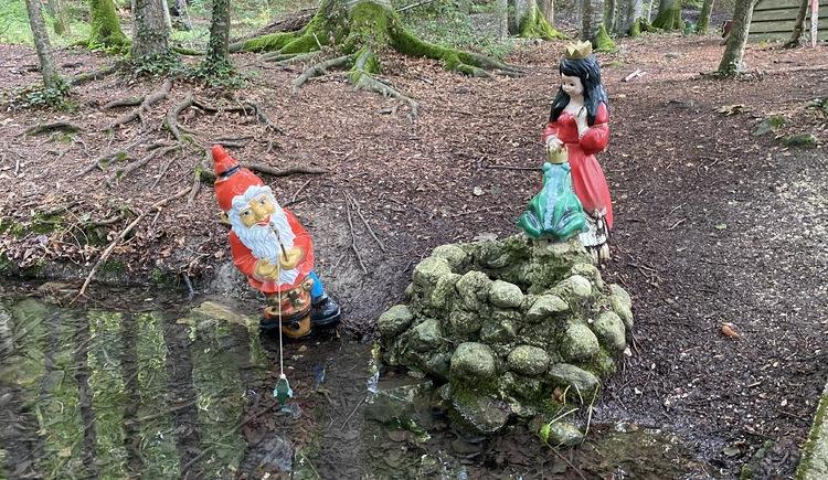 Märchenwanderweg Zwerg angelt im Bach, Froschkönig auf einem Stein mit seiner Prinzessin. (© TVB Attersee-Attergau)