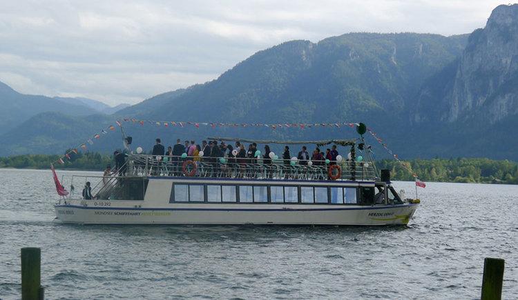 Schiff mit Hochzeitsgesellschaft an Board, im Hintergrund Berge. (© Mondsee Schifffahrt Hemetsberger)
