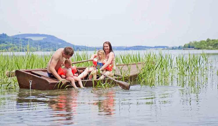 Familie im Ruderboot auf dem Irrsee, im Hintergrund das Schilf. (© Gaderer)