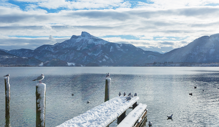 View over a snow-covered footbridge in front of the Mondsee with the Schafberg in the background. (© TVB Mondsee-Irrsee)