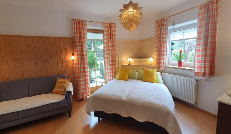 Helles, gemütlich eingerichtetes Schlafzimmer in der Ferienwohnung Dreimäderlhaus Dependance Bad Goisern. (© Gabriele Untersberger)