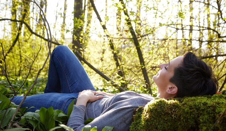 A woman enjoys the silence in the forest. (© Naturpark Attersee-Traunsee/Daniela Stockinger)