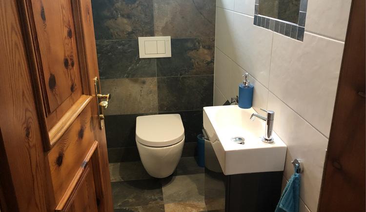 Separate Toilette ausgestattet mit Waschbecken und Fenster.