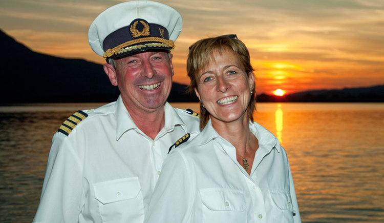 The captains Mr. and Mrs. Hemetsberger on a ship, in the background sunset. (© Mondsee Schifffahrt Hemetsberger)