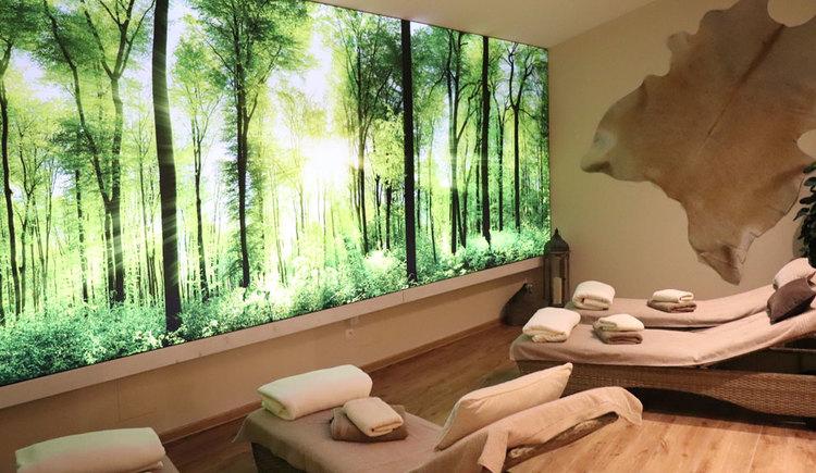 Ruheraum eines Wellness-Bereiches mit Liegen und Fotowand mit Waldpanorama