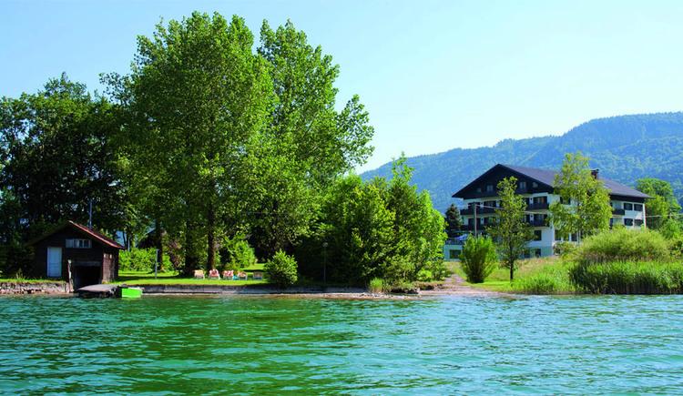 Blick vom See auf das Hotel davor Bäume und das Ufer. (© Seehotel Pöllmann)