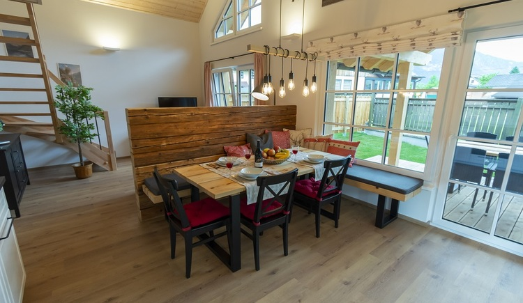 The dining area is seperated from the rest of the living room with a beautiful wooden wall of old stock, and invites you to a cozy get-together.