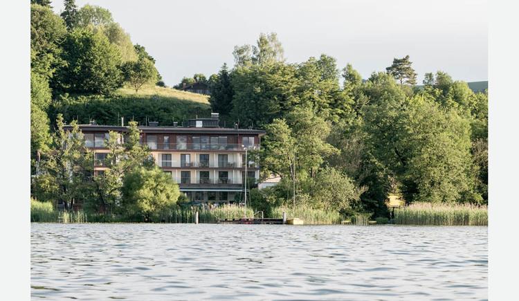Blick auf das Hotel vom See aus, Bäume. (© Lackner)