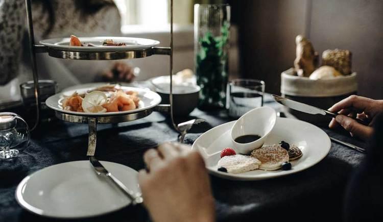 ein gedeckter Frühstückstisch, mit Gebäck, Wurst, und süßen Köstlichkeiten. (© Iris Porsche Hotel & Restaurant)