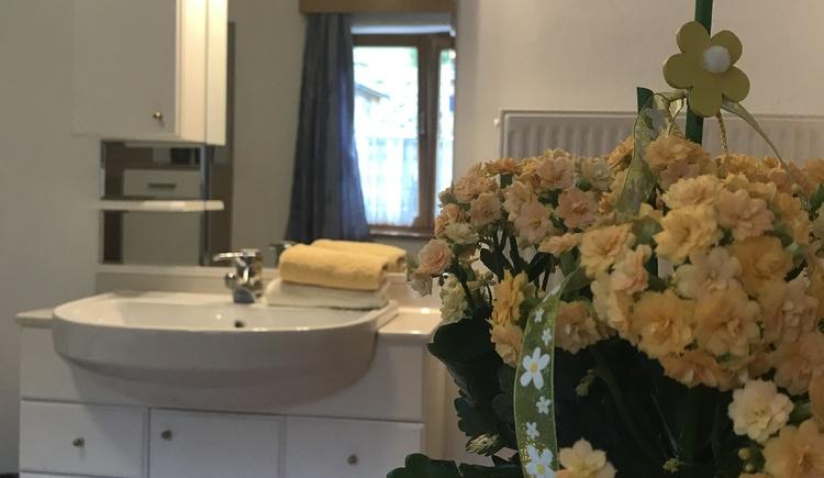 Die Aufnahme zeigt das Waschbecken vom Doppelzimmer 1 und einen Blumenstrauß im Vordergrund. (© Gerald Rastl)