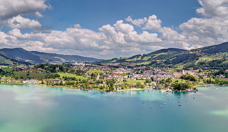 The beautiful blue Mondsee with some sailing boats in the harbor and the village of the same name in the background. (© TVB Mondsee-Irrsee)