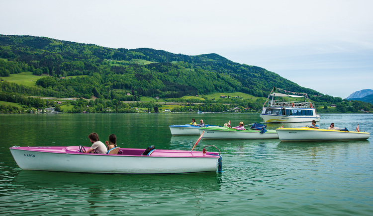 Boats on the lake, in the background mountain and meadow. (© Mondsee Schifffahrt Hemetsberger)