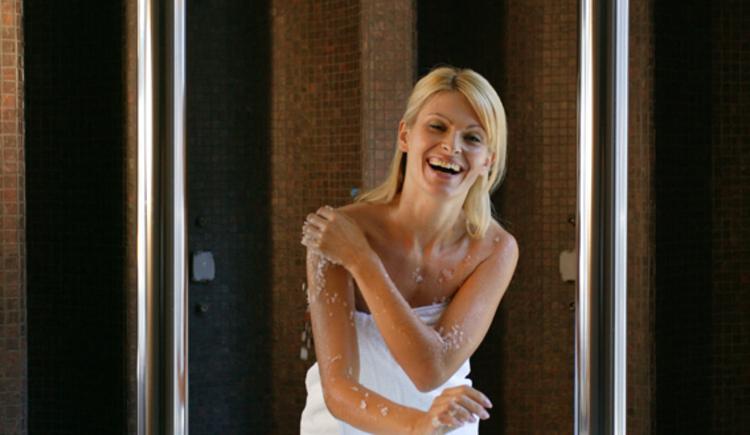 Frau kühlt sich bei der Crushed-Ice-Dusche im Saunabereich des Lebensquell Bad Zell ab.