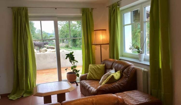 Wohnzimmer mit Couch, Tisch, Fenster und Tür zur Terrasse